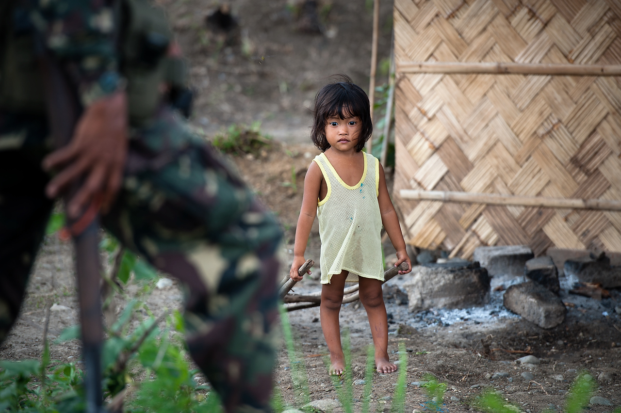 A child watches as the CAFGU member marches past her house. CAFGU paramilitary operate in vicinity of MILF rebel held territory. Often there is exchange of fire as patrols run into each other.