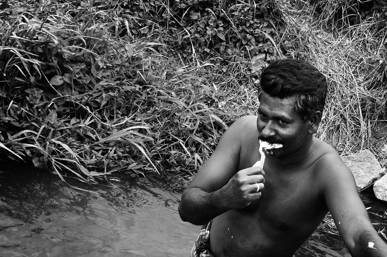 An Internally Displaced Person of Muttur brushes his teeth in the irrigation canal near the Railway station camp for displaced persons in Kanthale, Trincomalee.Fierce battle over Muthur town in eastern Sri Lanka between Tamil tiger rebels and the Sri Lankan forces pushed some 45,000 strong Muslim community into displacement.