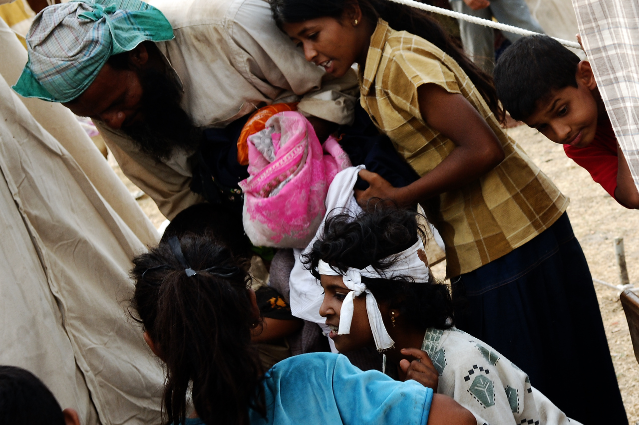 Wounded Internally Displaced girl browse through relief aid received by her family upon arrival at the camp for displaced persons in Kanthale.