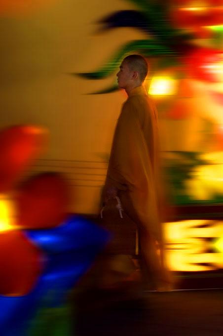 Buddhist monk walks past the Golden Temple, Singapore