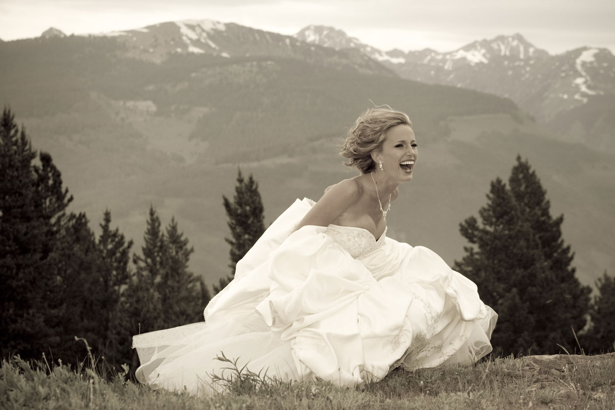 Bride ducking from wind at Eagle's Nest on top of Vail Mountain. Wedding Photography by Toni Axelrod.