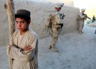An Afghan boy watches as U.S. Marines from the 1st Battalion 2nd Marines conduct a foot patrol through a village outside of Musa Qala in Helmand Province, Afghanistan. June 2010.