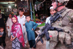 A soldier from Bravo Company, 2nd Battalion, 18th Infantry Regiment, walks past a group of children on patrol in Imam Sahib, Afghanistan. July 2011.