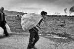 A Syrian refugee carries a bag outside of his camp in Reyhanli, Turkey. March 2012.