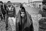 A Syrian refugee wears a coat over his head outside of his camp in Reyhanli, Turkey, March 2012.
