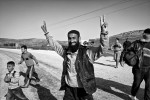 A Syrian refugee celebrates after crossing into Turkey near a refugee camp in Reyhanli, Turkey. March 2012.