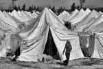A Syrian refugee leaves a tent in a refugee camp in the town of Reyhanli, Turkey. March 2012.