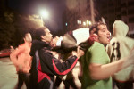 Demonstrators carry victim away from street clashes with riot police in downtown Cairo, Egypt. January 2011.