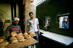 Customers look through a window while waiting to buy bread at a small bread factory in a poor neighborhood in Cairo. June 2008.
