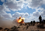 Rebel fighters fire a rocket toward governmet troops on the frontline, near Brega, Libya. March 2011.