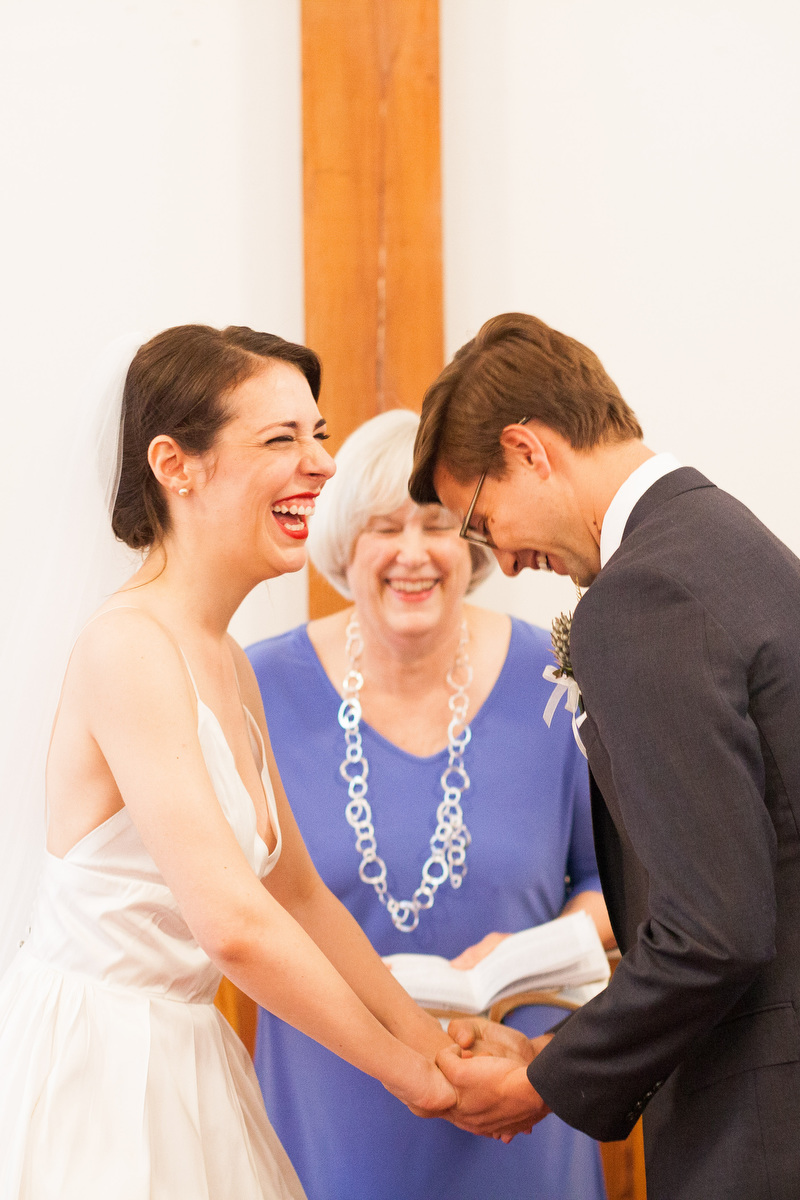 Two people laugh during their wedding ceremony in Charlottesville at Woolen Mills Chapel