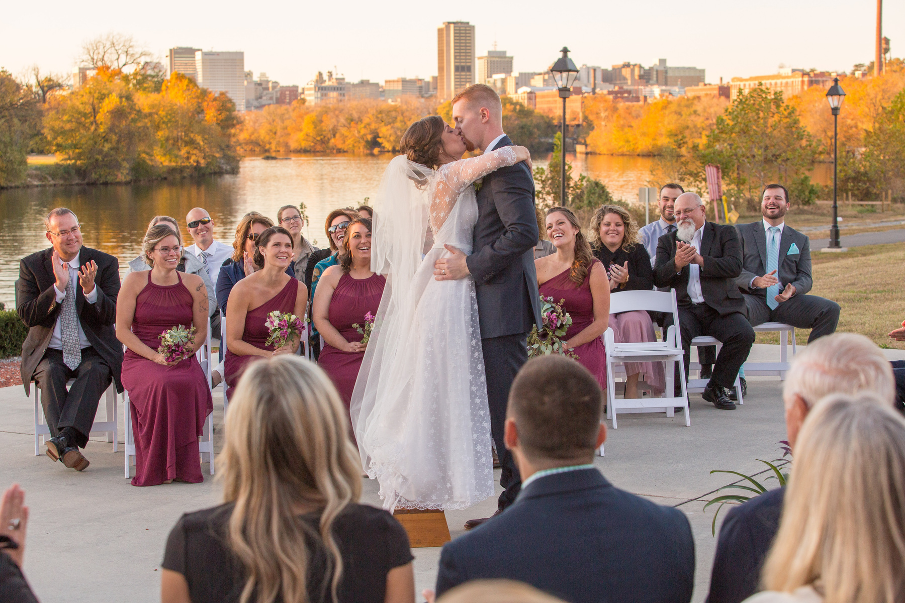 A bride and groom kiss at the close of their wedding ceremony at The Boathouse at Rocketts Landing in Richmond, Va