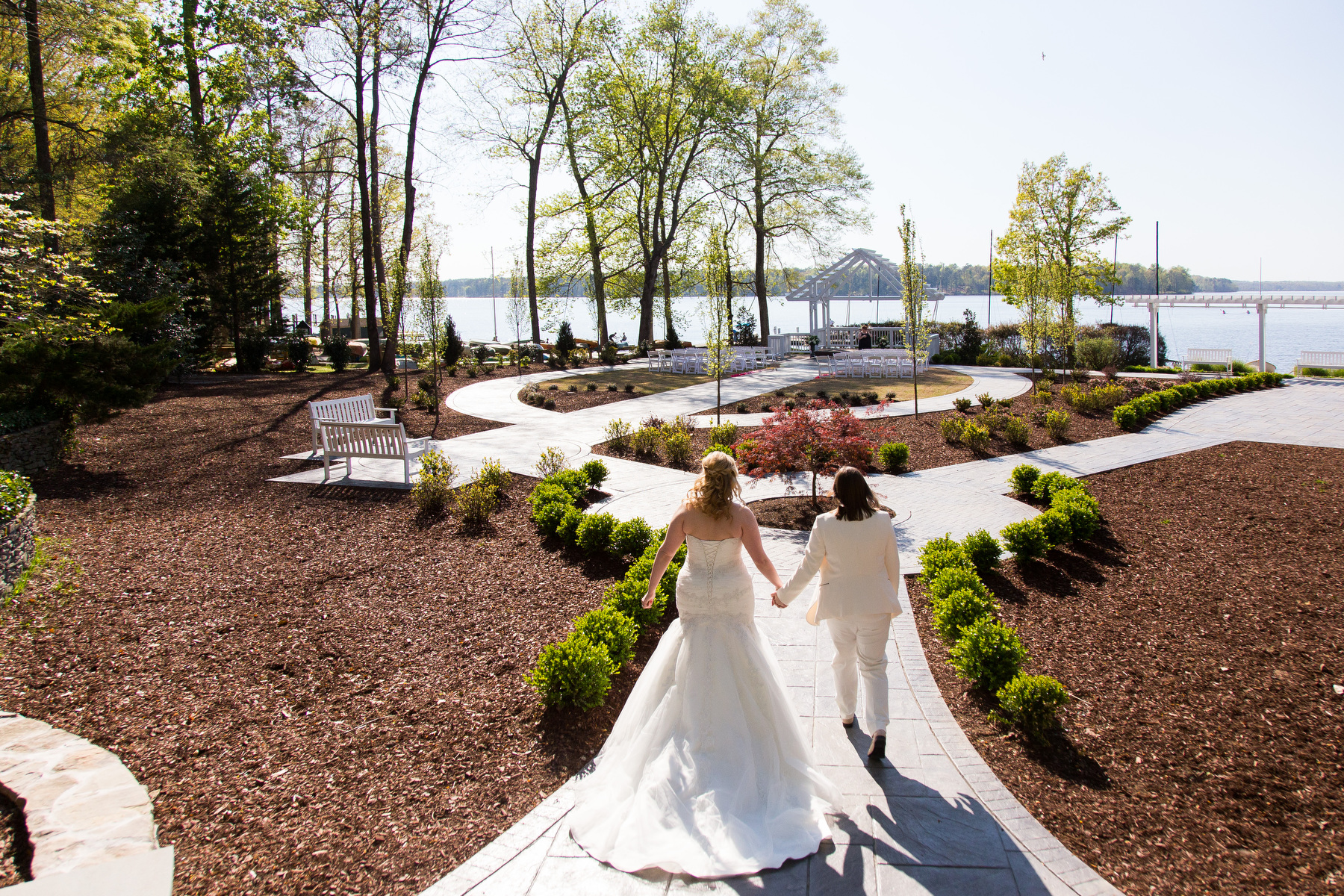 Two brides walk towards their wedding ceremony site at The Boathouse at Sunday Park