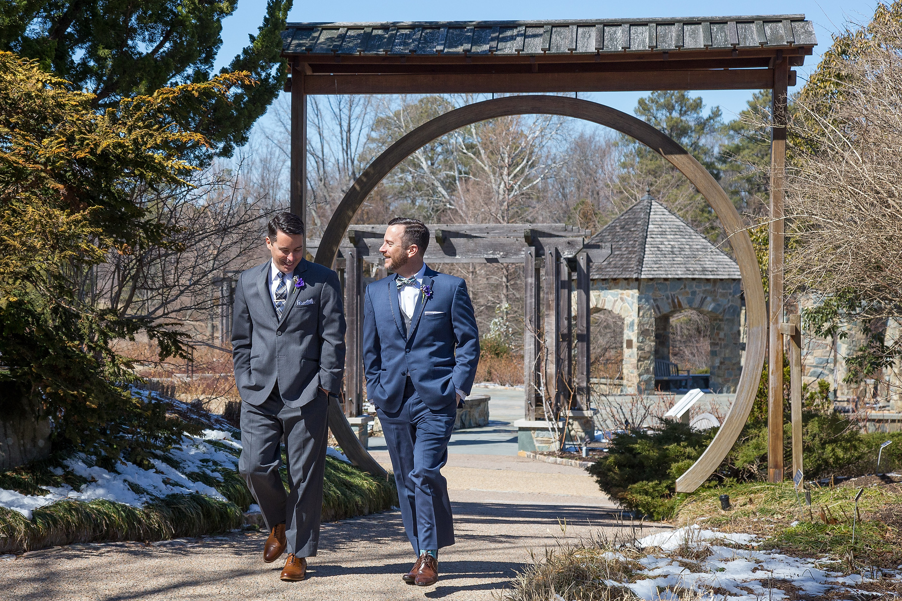 Two grooms walk to their wedding ceremony at The Lewis Ginter Botanical Garden in Richmond Va