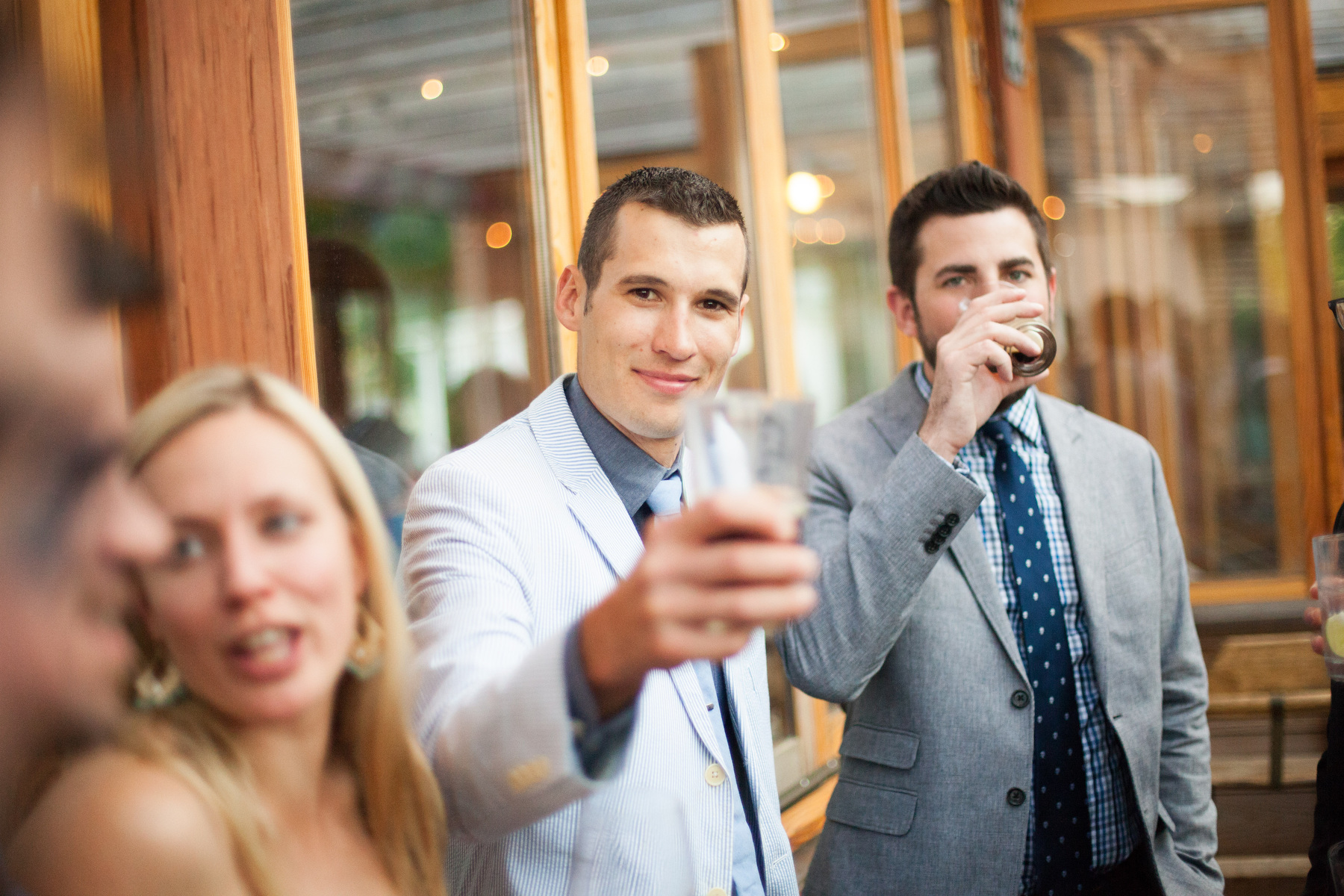 A man raises his glass during a wedding reception at The Local in Charlottesville, VA