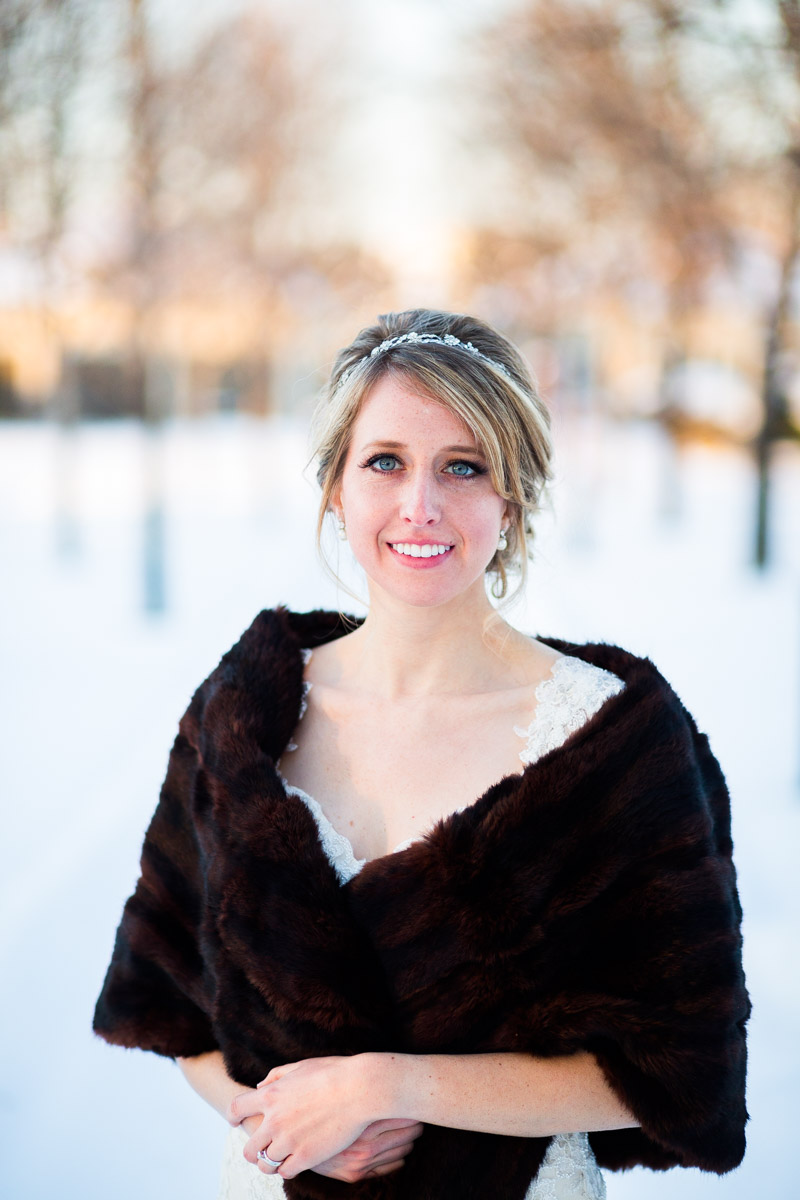 A bride poses for a portrait after her wedding in the snow at The Dominion Club in Richmond VA