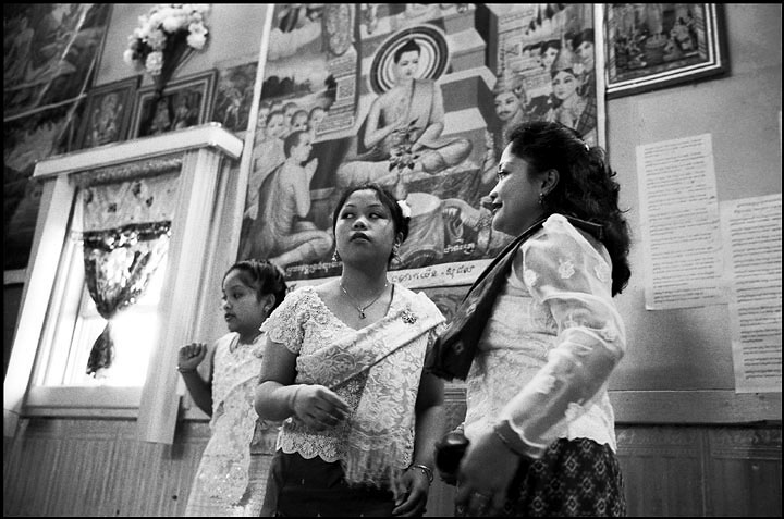 A mother and her two daughters rise together after a long ceremony. Behind them are huge paintings that depict the life story of Shakyamuni Buddha.