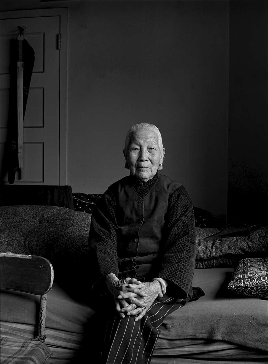 Mrs. Chiu, an elderly Chinese woman, sits on the bed  in her apartment on Pearl St. in New York Chinatown, 1981.