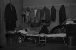 A man sleeps on his bed in the Bachelor Apartment he shares with 3 other men, Bayard St., New York Chinatown, 1982. He is surrounded by his belongings, including coats and jackets hangin on the well above him.