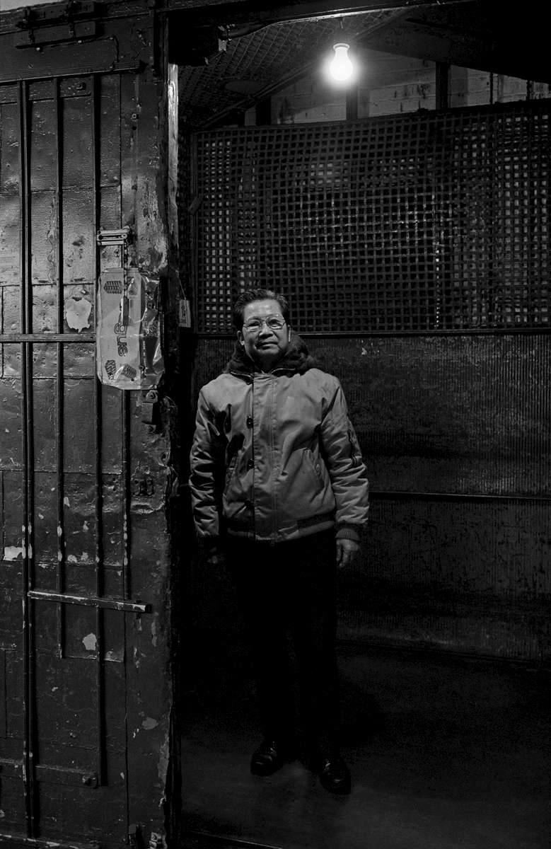 Elevator operator stands in garment factory elevator lit by a single light bulb. 202 Centre St., New York Chinatown, 1983