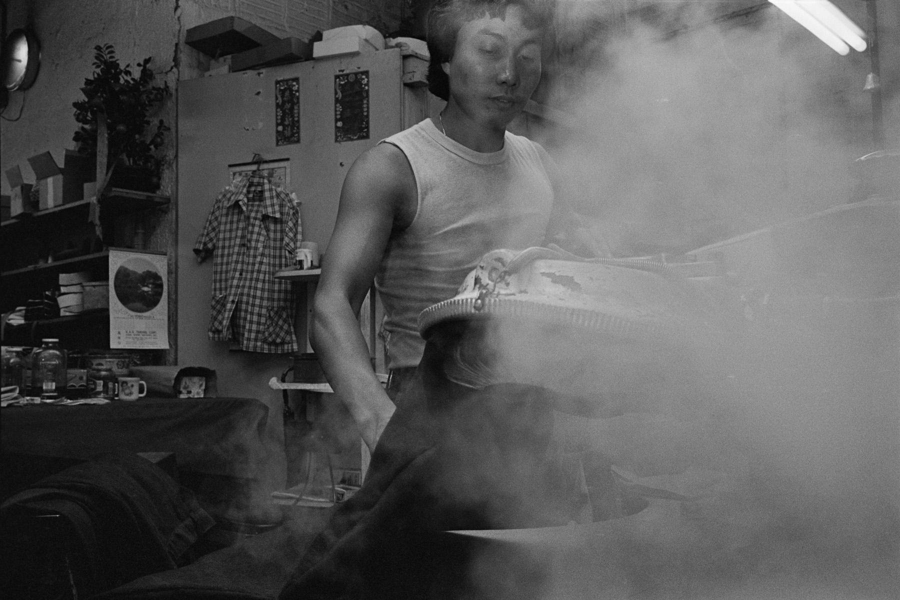 Mo, seen in a fog of steam,  presses a garment at Geolan Sportswear, a garment factory, 202 Centre St. New York Chinatown, 1983
