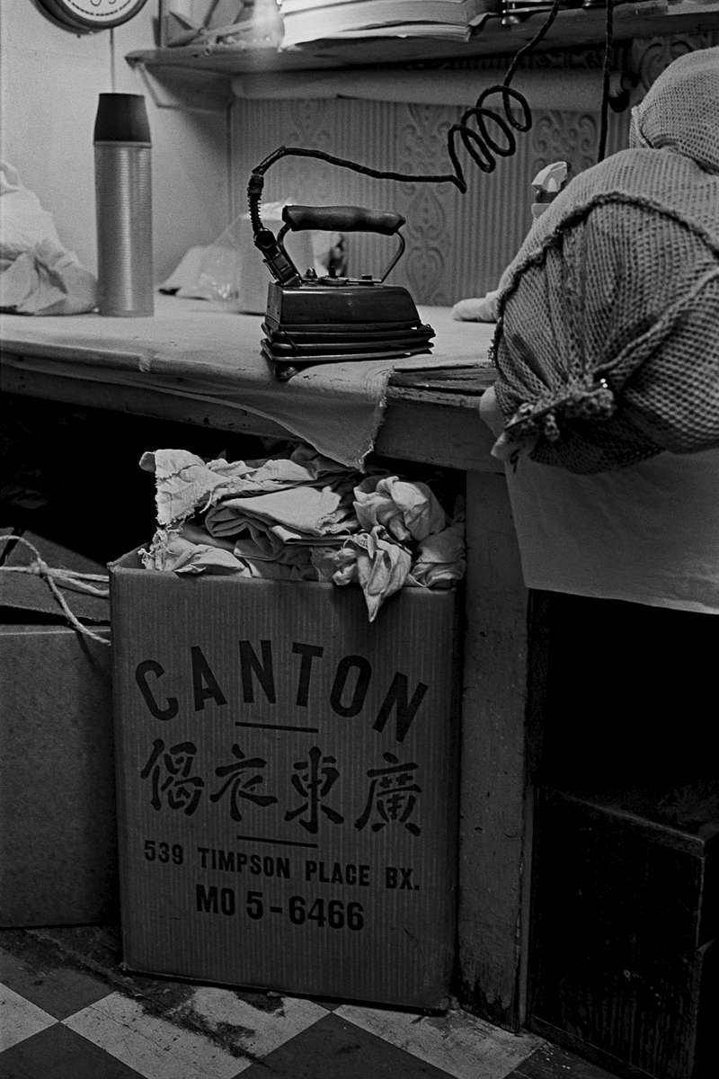 A view of the counter with a clothes iron, laundry bag, thermos and a large cardboard box. Sam Wah Laundry, 1980 Creston Ave., Bronx, New York, 1982