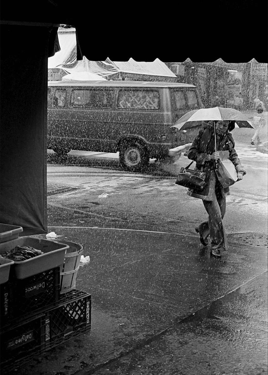 Catherine and Henry St., New York Chinatown, 1982.A woman with an umbrella walks in a snow storm. She is seen form inside, framed by the entrance to Frankie Wong's seafood stre at Catherine and Henry St., New York Chinatown, 1982.