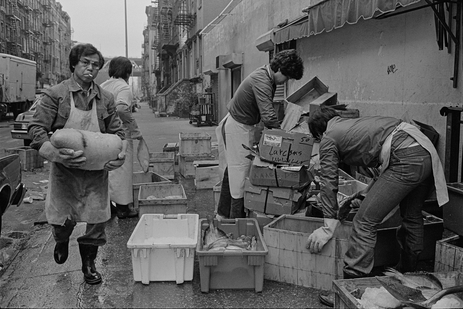 Men working outside on the sidewalk at Catherine and Henry St., New York Chinatown, 1982. On the left side a man smoking a cigarette carries a bag of scallops while other men sort through boxes of seefod. Looking down Henry St. toward the Manhattan Bridge.