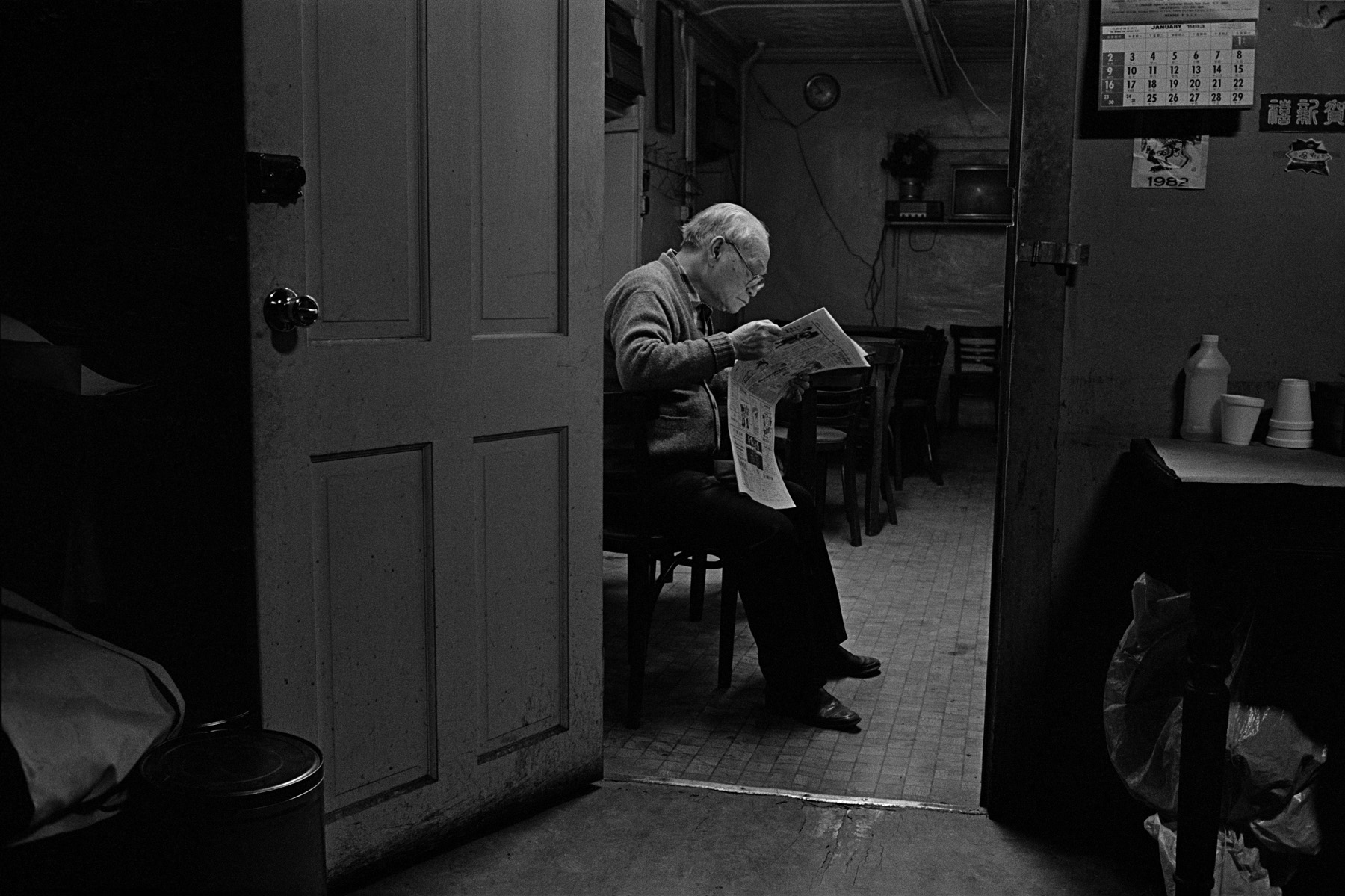 Mr. Ng sits in a doorway reading a newspaper in the apartment he shares with 3 other men on Bayard St., New York Chinatown, 1982.