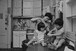 Rebecca with her children in their kitchen, New York Chinatown, 1982.