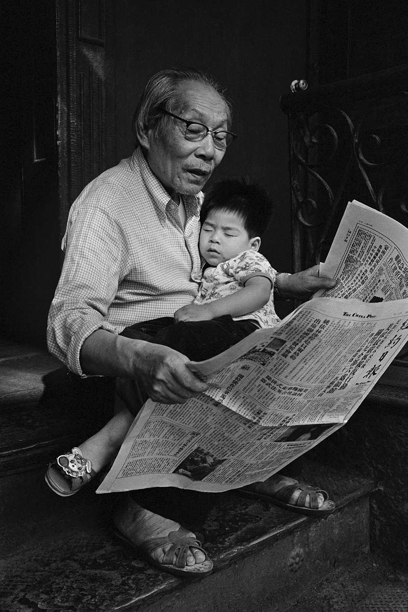 Kam Ho Lee, an elderly Chinese man, sits on the stoop of his apartment building, reading the newspaper, with his gandson, Vincent Lee, sleeping in his lap.