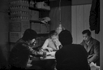 Men playing Mahjong in the back room of  Frankie Wong's butcher shop, Fook Hing Long, 27 Catherine St., New York Chinatown, 1981. Frankie's is seen in silhouette with his back to the camera.