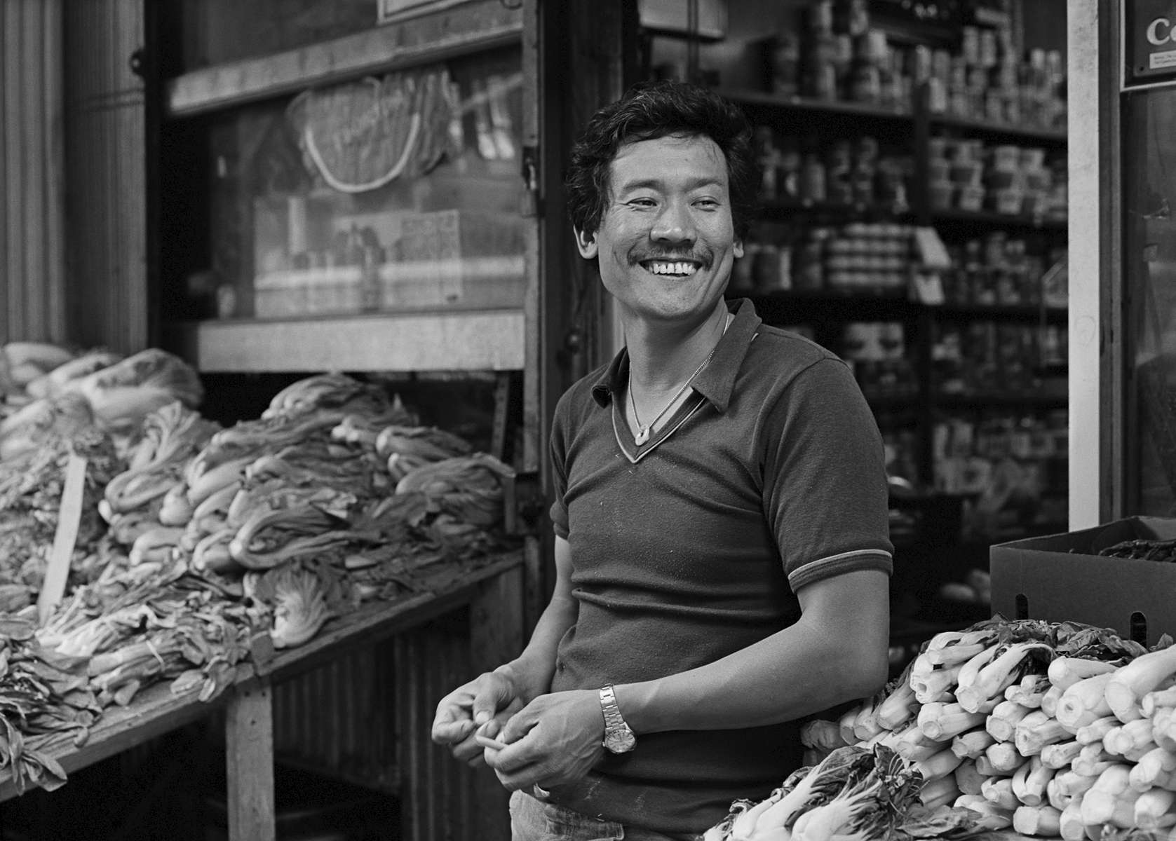 Frankie Wong in front of his grocery store on Catherine St., New York City, 1981.