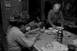 3 men at the common table eating dinner in Bachelor Apartment, they share on Bayard St., New York Chinatown, 1982