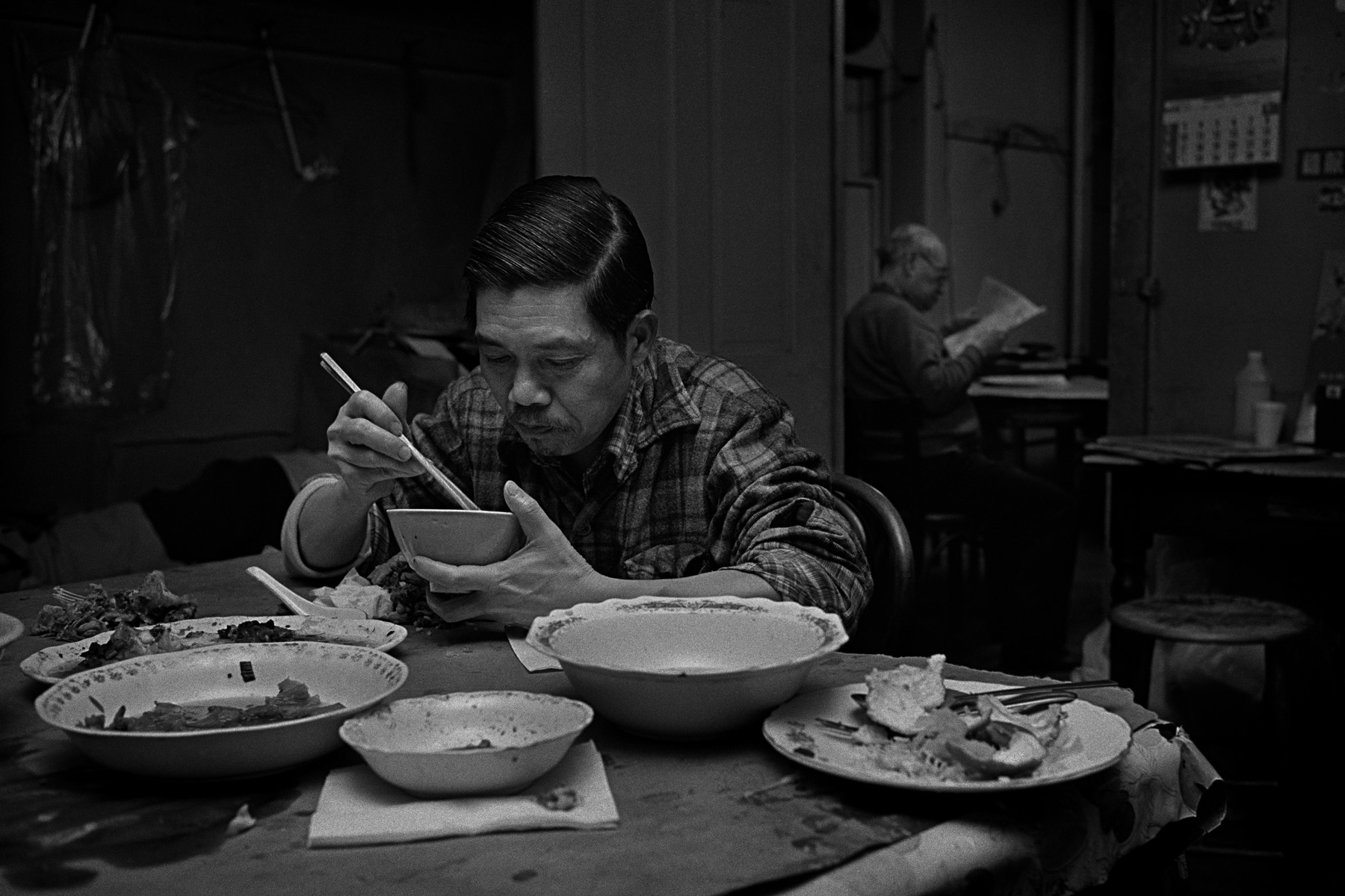 A man eats dinner at the common table in the Bachelor Apartment he shares with 3 other men on Bayard St. in New York Chinatown. Mr. Ng read a newspaper in the doorway in the background. 1982