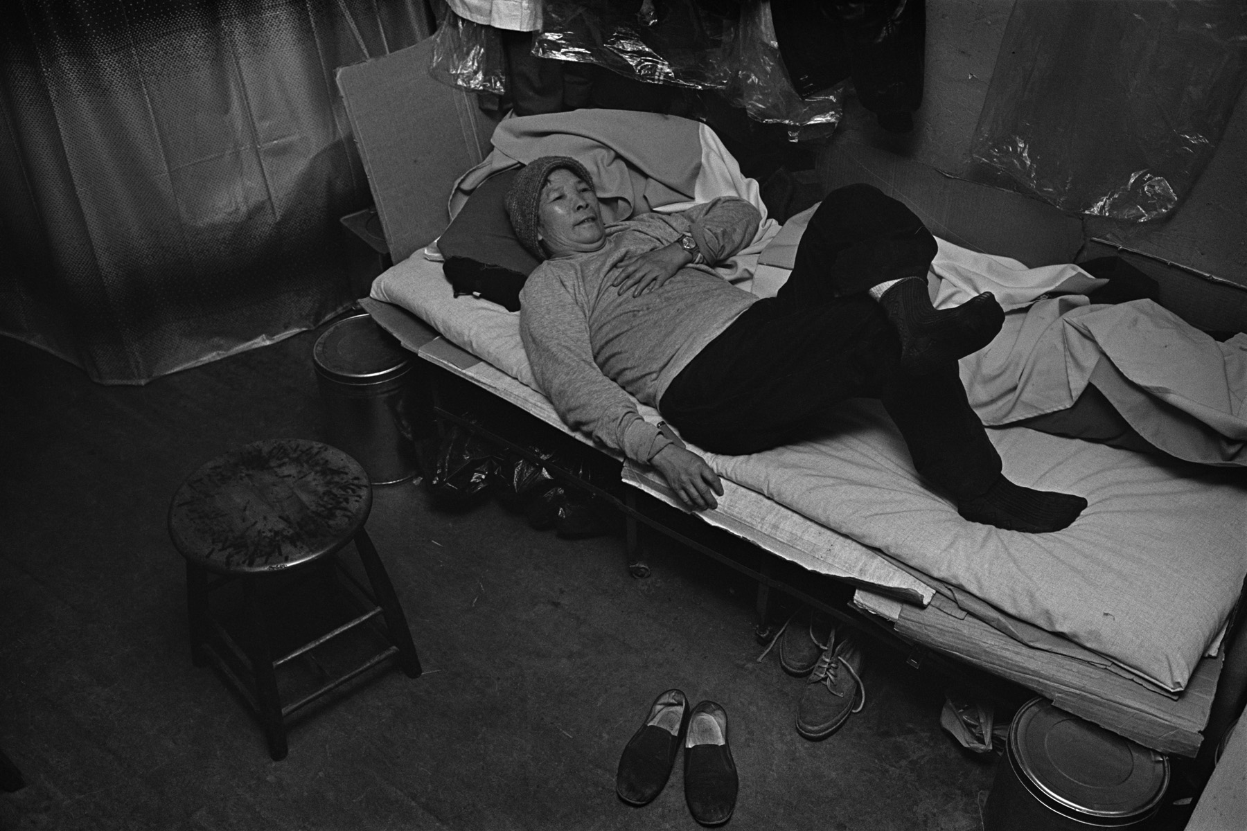 A man lies on his bed in theBachelor Apartment that he shares with 3 other men, Bayard St., New York Chinatown, 1982.