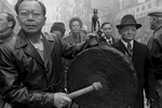 A group of men in Bayard St. during a Lunar New Year celebration in New York Chinatown in 1984. In the foreground a man is beating on a large gong.