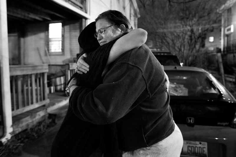 Ellen is comforted by a home health aide after her mother's body is taken from the house.