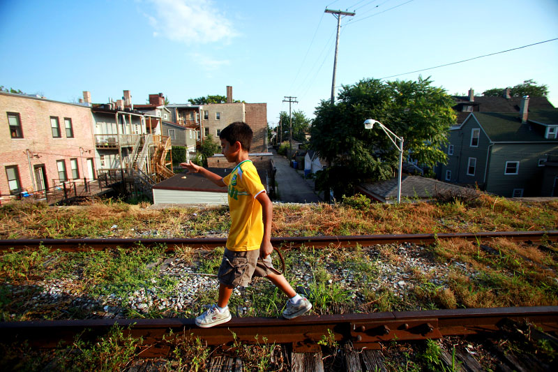 Jesse Davila, 7, of Manhattan, Kansas, walks along the railroad tracks on the Bloomingdale Trail in Chicago's Humboldt Park neighborhood. The three-mile stretch of land that is situated 15 feet above street level cuts through neighborhoods of varying gentrification and development on Chicago's west side.