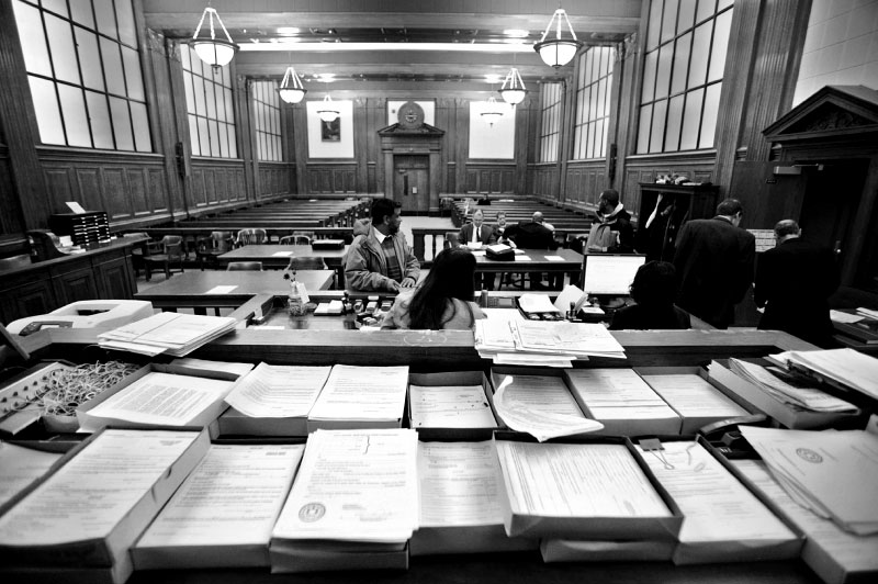 Paperwork fills the judge's bench and surrounding tables in small claims court at the Milwaukee County Courthouse. Here, landlords and tenants can attend hearings to discuss legal matters, such as eviction.