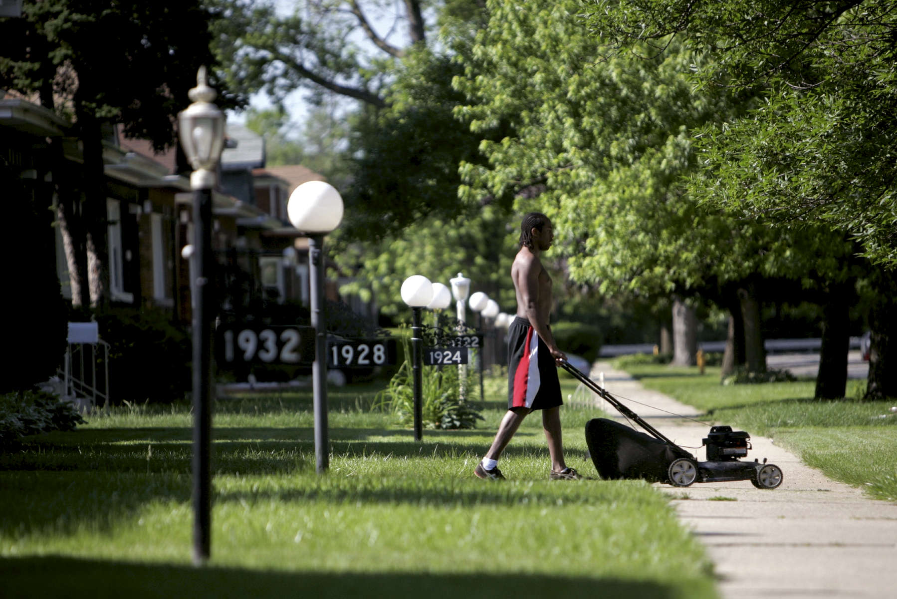 Carl Foreside, 19, home for the summer after his freshman year at the University of Iowa, mows the lawn of his family home on 11th Avenue in Maywood, Illinois. Numerous houses on 11th Avenue and the surrounding streets are boarded up due to foreclosure. In a town of about 27,000 residents, 1500 housing units are in foreclosure, some of which are owned by US Bank.