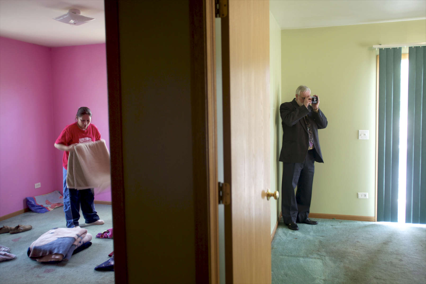 Blanca Lopez gathers her belongings before moving out of her foreclosed home while realtor Joseph Laubinger takes photographs to show that the property has been vacated. In addition to selling homes, Laubinger works with banks to make sure homeowners in foreclosure move out of the homes.