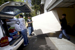 Israel Lopez, left, packs his belongings in the family minivan as neighbors help him move out of his foreclosed home.