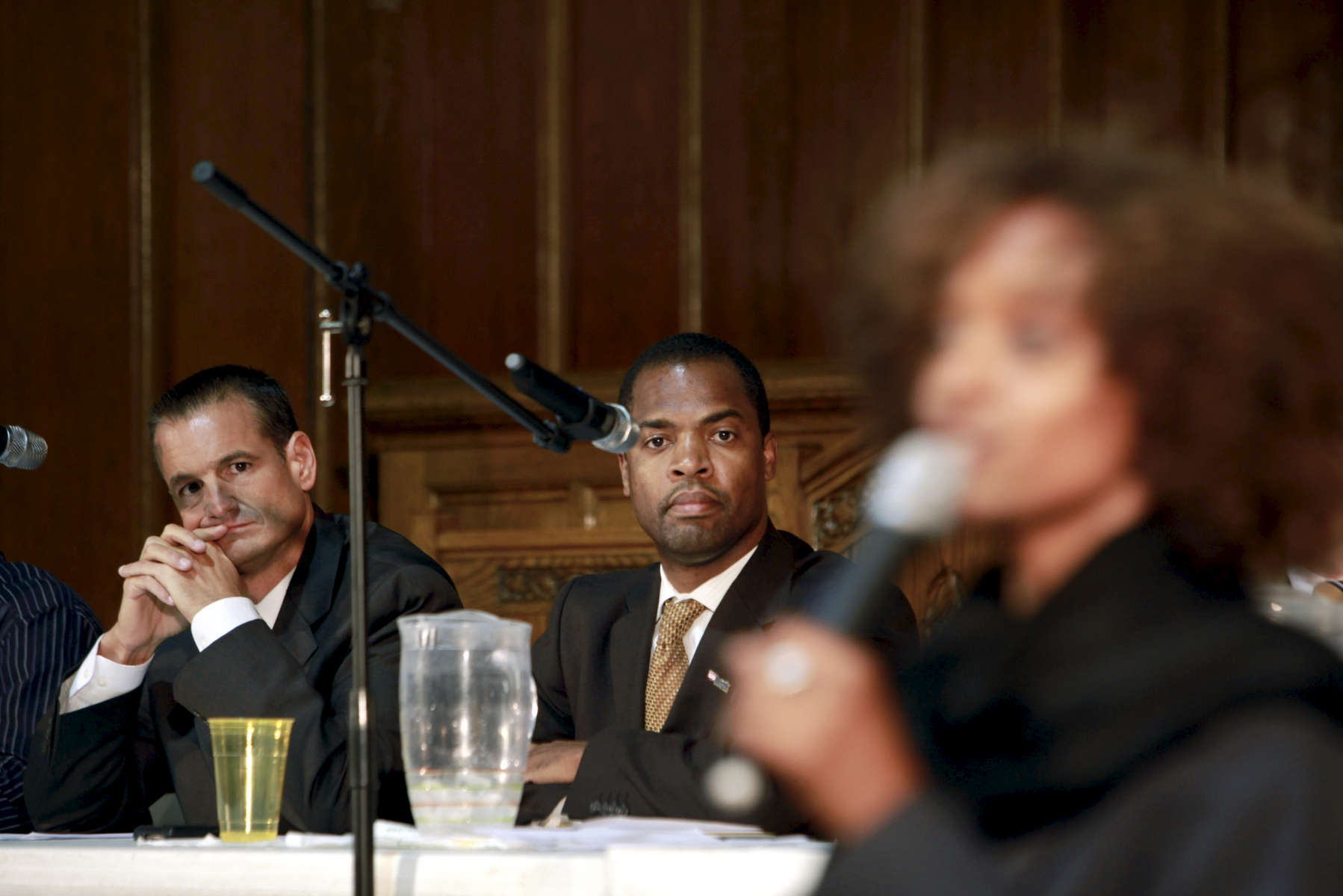 William Fanter, left, senior vice president and Chicago regional manager of US Bank and Robert V. McGhee, vice president of community development, listen as community members and local politicians discuss the foreclosure crisis on Chicago's west side and in neighboring Maywood, Illinois.