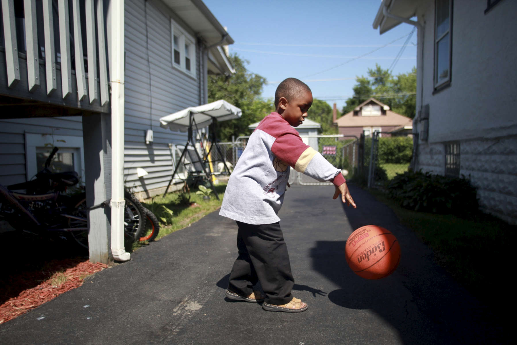 Kanye Hankinson, 5, plays in the driveway of his Maywood home, which his father, William Hankinson, is trying to save from foreclosure. In a town of about 27,000 residents, 1500 housing units are in foreclosure, some of which are owned by US Bank. Mr. Hankinson says US Bank is working with him to adjust his mortgage so he can remain in the home.