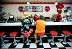 Americana, Coca Cola, Coke, fountain, counter, soda, checker, tile, stools, bar, drinks, t-shirts, clock, menu, hawaiian shirt, straw hat, tourists
