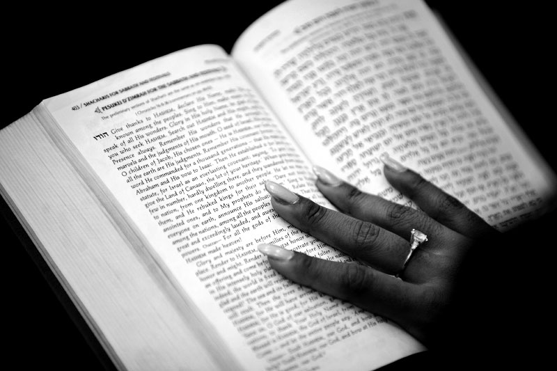 Tamar Manasseh, 29, follows along in the Jewish bible during Shabbat service at Beth Shalom B'nai Zaken Ethiopian Hebrew Congregation.