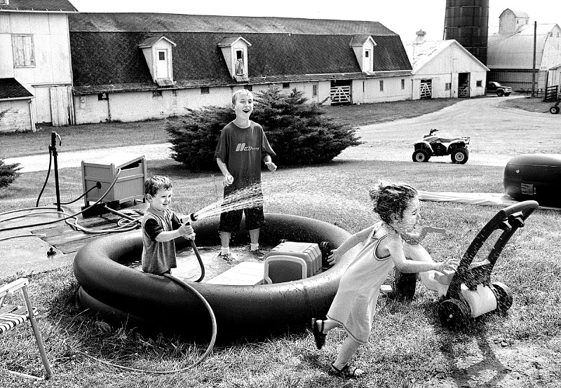 Austin Collins, 2, of Oswego, Tim Collins, 10, of Yorkville and Makenzie Ervin, 3, of Plano play in the wading pool at Austin's home in NaAuSay township just outside of Oswego, Illinois.