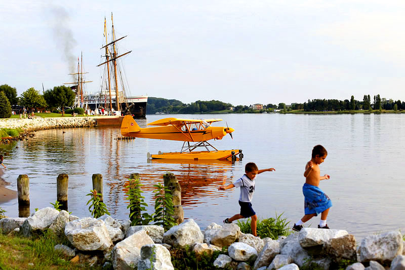 Children play on the shore of Lake Michigan where the Pride of Baltimore II, a reproduction of an 1812-era Baltimore-built topsail schooner privateer, is docked by the S.S. Badger.