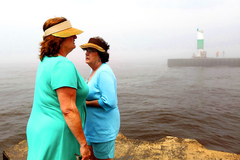 Deborah Torrice, left, and Penny Smedley, both from Chelsea, Michigan visit the South Pier Lighthouse in South Haven, Michigan. The women have been visiting South Haven's beach since childhood.